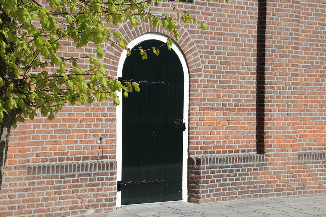 Authentieke deur in de hervormde kerk van nieuw buinen die net opnieuw is geschilderd